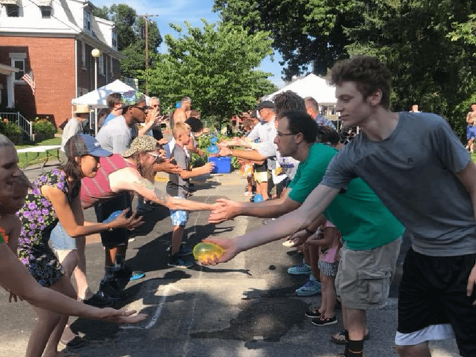 people playing a water balloon toss game