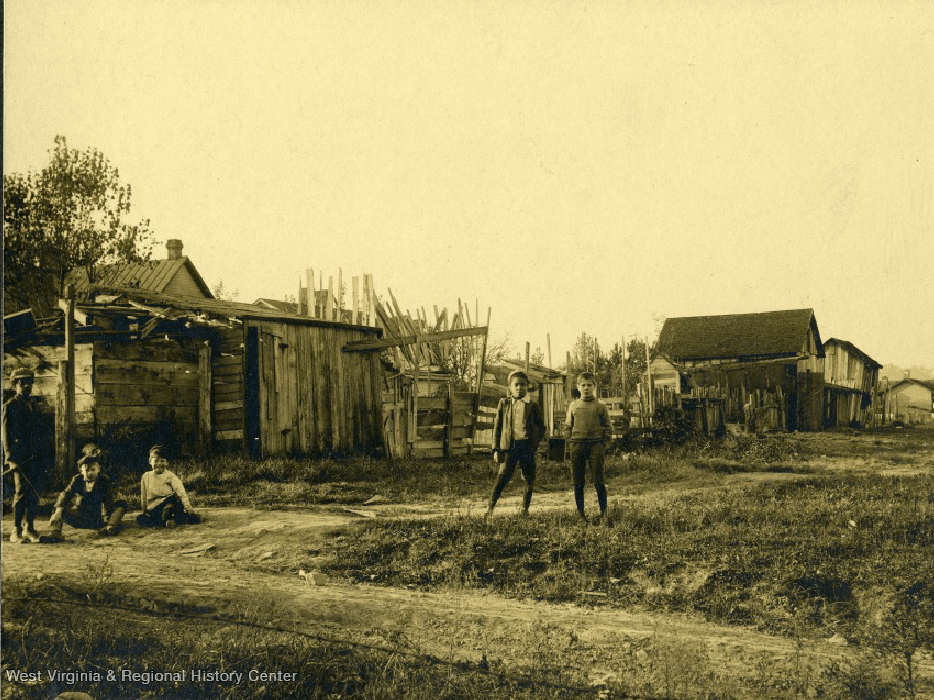 old photo of people standing near old houses